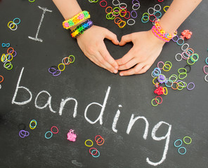 childs hands forming a heart with loom band bracelets on a black