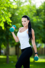 Portrait of cheerful woman in fitness wear exercising with