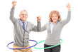 Mature man and woman exercising with hula hoop