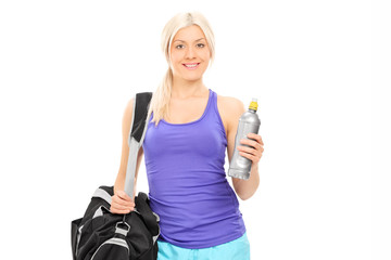 Female athlete holding a water bottle and carrying a sports bag