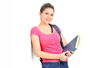 Female student holding books and leaning on a wall