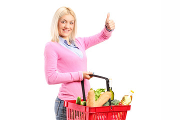 Girl holding a shopping basket full of groceries and giving a th