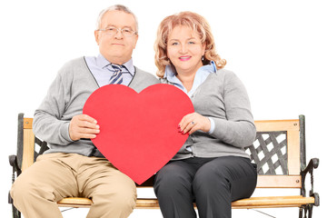 Lovely mature couple holding big red heart seated on bench