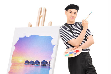 Male artist standing by a painting on an easel