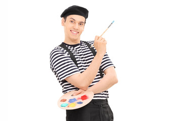 Male painter holding a paintbrush and leaning against a wall
