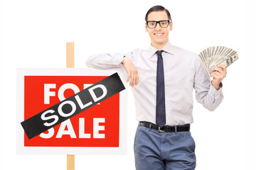 Male realtor holding money next to a sold sign