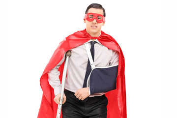 Male superhero with broken arm and a leg