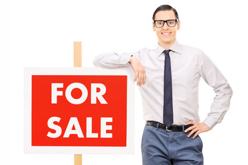 Man leaning on a for sale sign