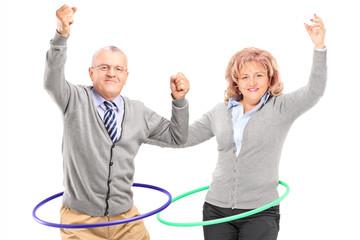 Mature man and woman exercising with hula hoop