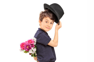 Profile shot of a cute little boy holding flowers behind his bac