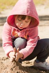 Девочка играет песком