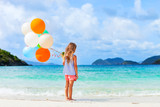 Fototapety Back view of little girl with balloons at beach