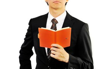 メモ帳を持っている黒いスーツのビジネスマン