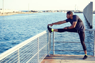 On sea background muscular build man doing legs stretching