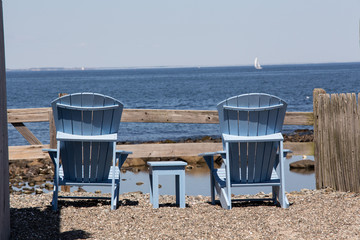 two adirondack chairs on the beach