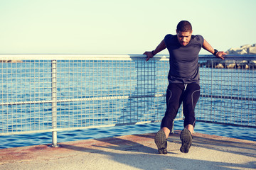 Sporty athletic runner doing pull-ups lying on the pier railing