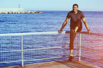 Athletic runner doing legs press on evening training outdoors