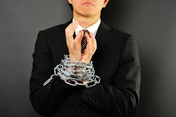 鎖で手を縛られたアジア人のビジネスマン