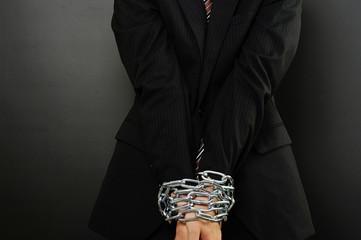 鎖で縛られたスーツの男性