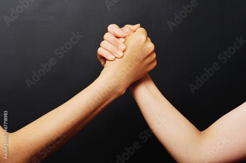 黒い背景で撮影した男女の握手