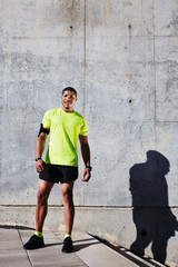 Sportsman with running armband on arm resting tired after run