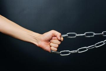 黒背景で撮影した鎖を引く手