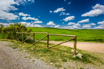 Old wooden fence, dirt road and green field