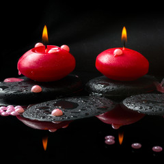 spa concept of  red candles and pearl beads on zen stones with d