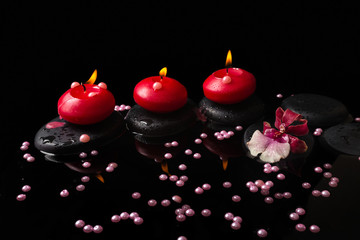 spa concept of red candles, zen stones with drops, orchid cambri
