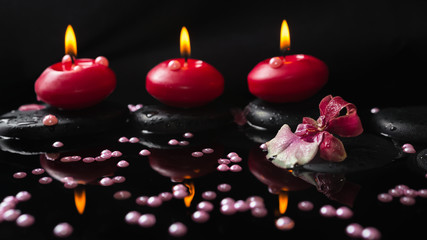 spa still life of red candles, zen stones with drops, orchid cam