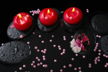 spa concept of red candles on zen stones with drops, orchid camb