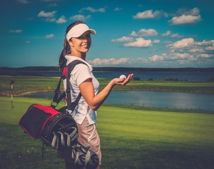 Young cheerful woman with bag and ball on a golf field