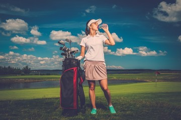 Young woman drinking water on a golf field