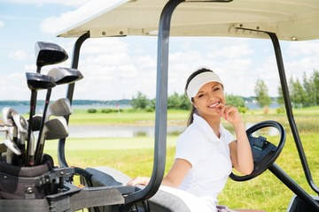 Young cheerful woman driving golf cart