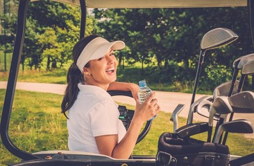 Young cheerful woman with bottle of water driving golf cart