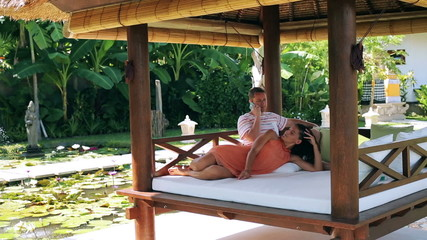 Couple lying on bed and talking on cellphone in exotic garden