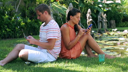 Couple sitting on grass in exotic garden and using cellphones