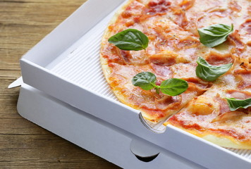 traditional Italian pizza with prosciutto ham and basil