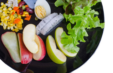 fruit and vegetable salad in black plate on white background