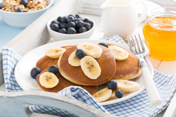 pancakes with banana, honey and blueberries for breakfast