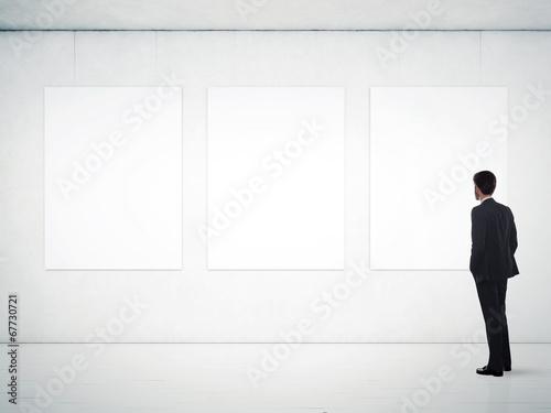Leinwanddruck Bild gallery room and man looking at empty frames