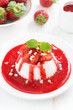 Vanilla panna cotta with strawberry sauce and nuts, top view