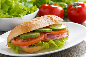 sandwich with ham and fresh vegetables on a plate