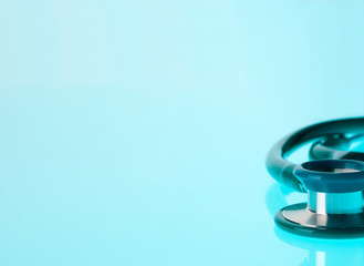Stethoscope on blue, reflective background