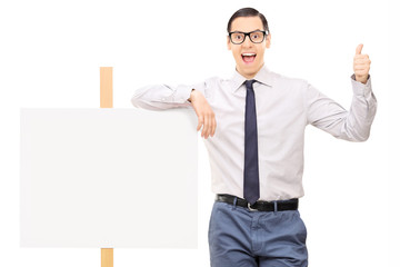 Excited man giving thumb up and standing by a blank signboard