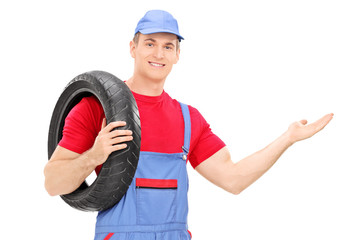 Male mechanic holding a tire and gesturing with hand