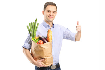 Man holding a bag of groceries and giving thumb up