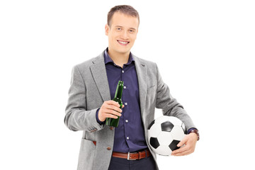 Man holding a beer bottle and a football