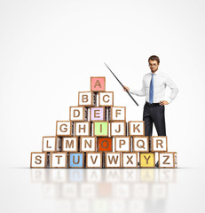 young teacher and colorful letter blocks