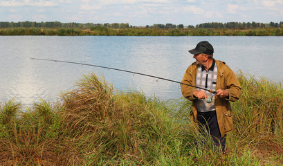 old fisherman with spinning rod on lake